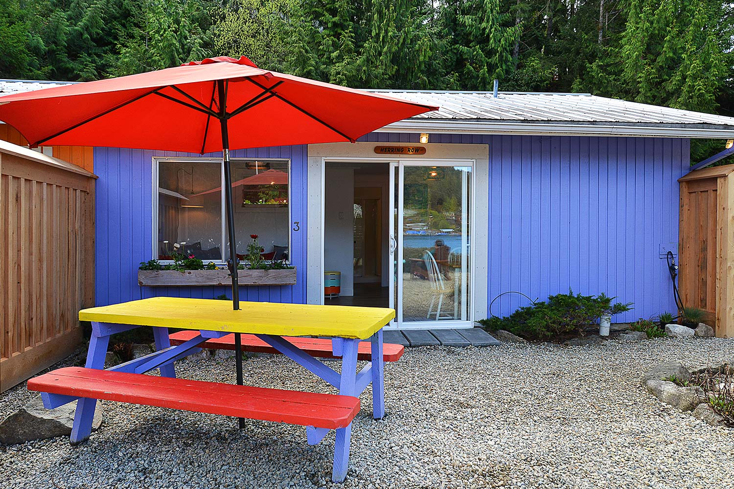 The front yard of Herring Row has a BBQ & picnic table. This purple cottage is one of 4 charming cottages at John Henry's.