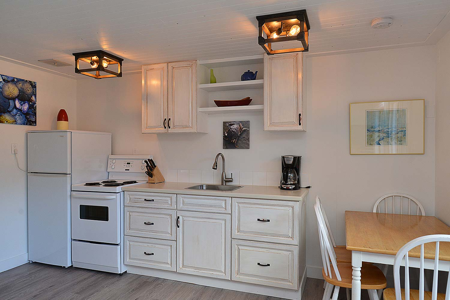 A coffee maker, stove, refrigerator, & dining table in the kitchen at this waterfront cottage for rent at John Henry's.