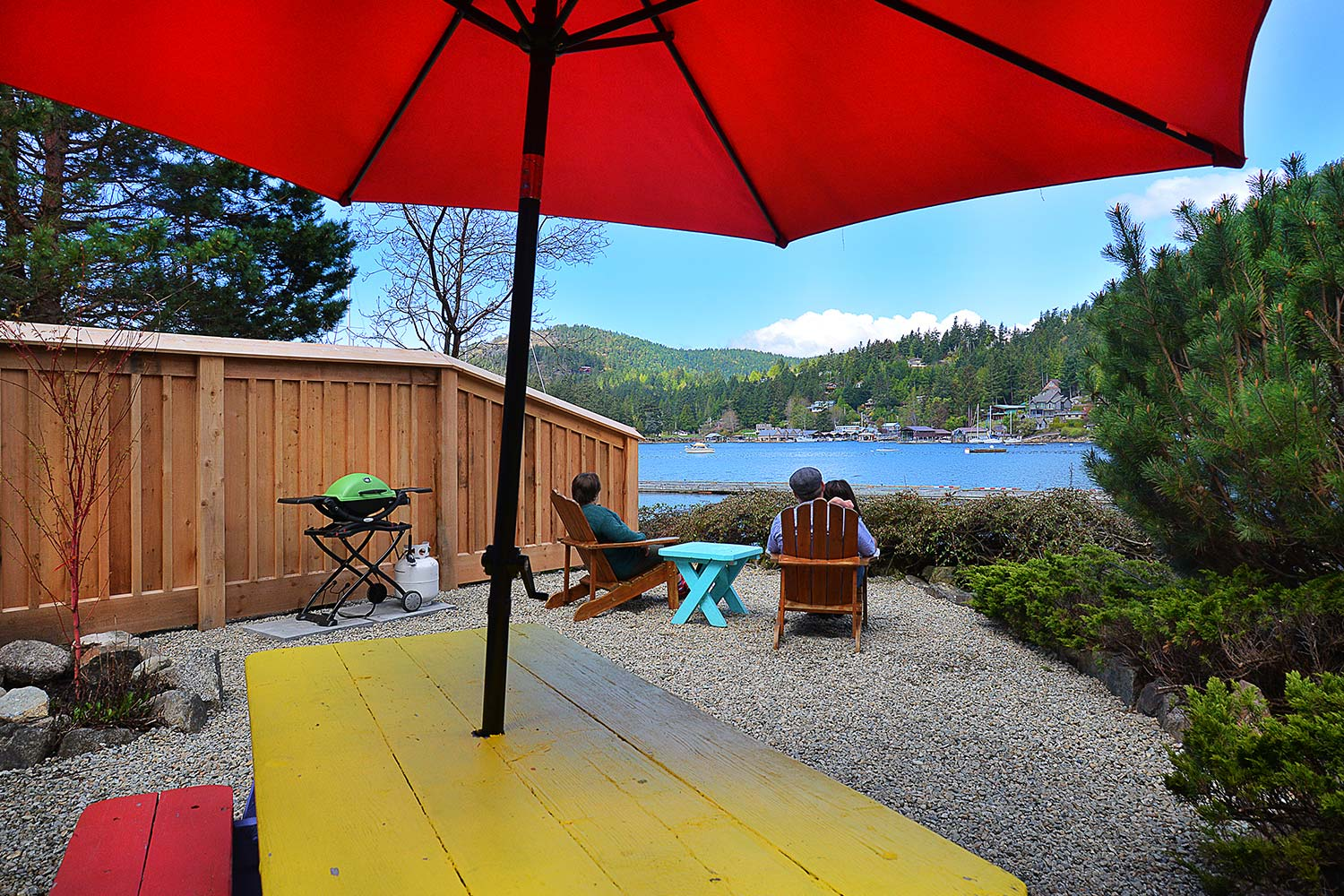 Two guests at the Herring Row oceanview cottage enjoy views of the Harbour from their front yard, which features a Weber BBQ.