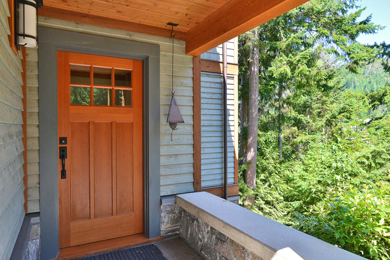 The front door of John Henry's luxury home rental, House 65, with a pine forest in the background.