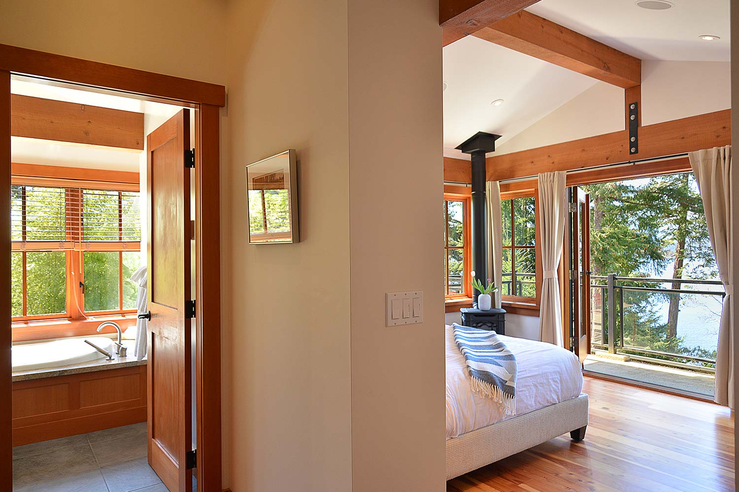 The bedroom of this oceanfront house rental has incredible views of the harbour and a nearby bathroom with a large bath.