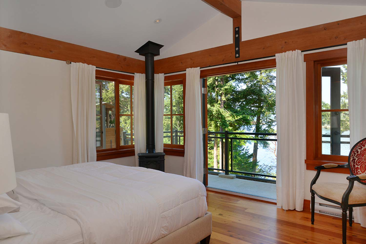 The upstairs master bedroom of this luxury holiday house features a private balcony with ocean views & a walk-in closet.