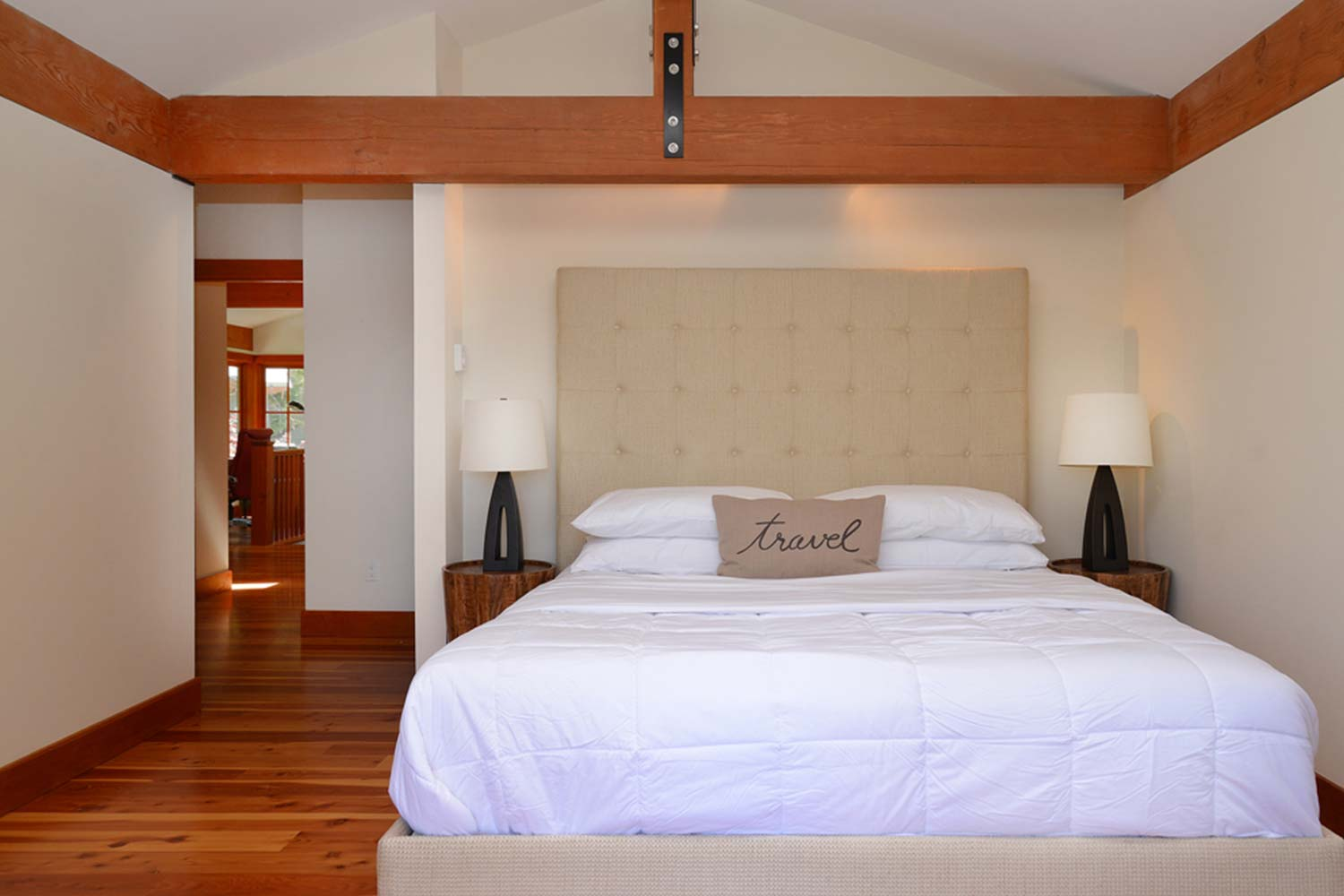 The bed in the master bedroom of this vacation luxury home has quality linen and a pillow that says Travel in the center.