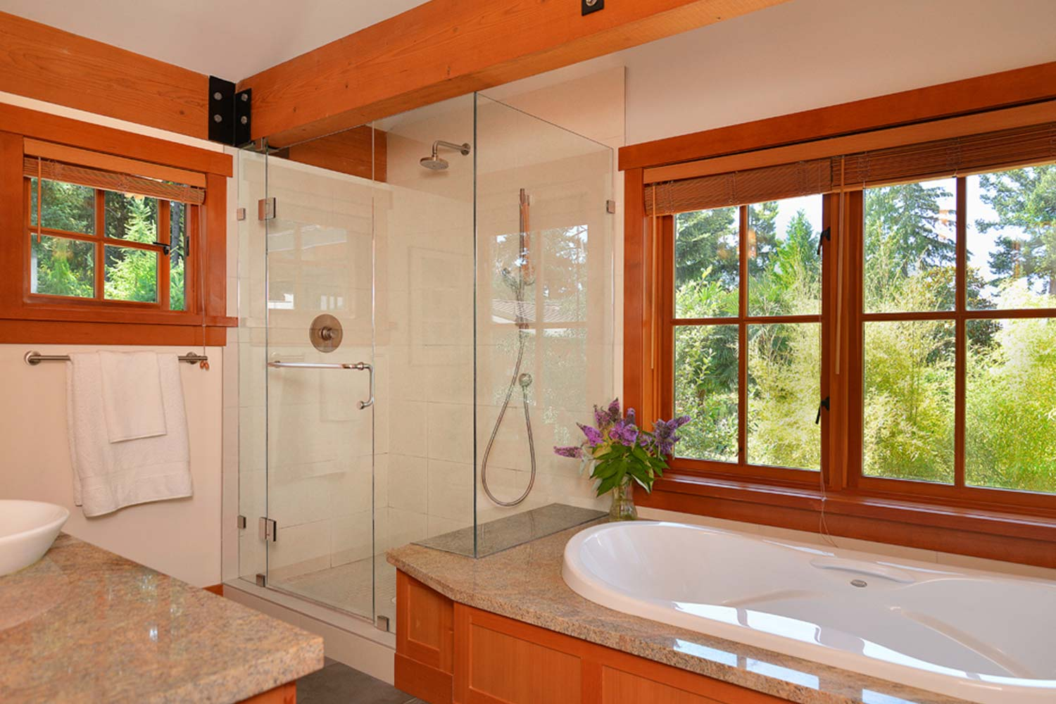 A bathroom in House 65 - a furnished home for rent, features a large bath, a shower, and a view of the surrounding forest.