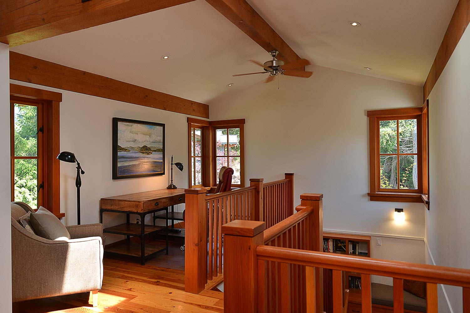 The upstairs office area in House 65 at John Henry's Resort and Marina has a large desk and artwork above it.