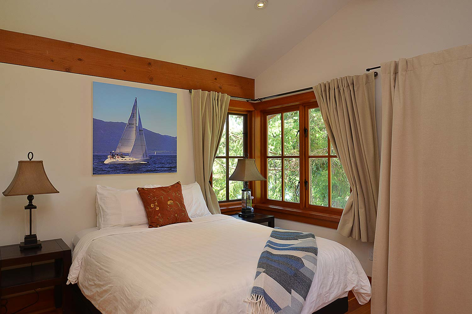 A bedroom in this large house rental has artwork of a sailboat above the bed and two bedside tables.