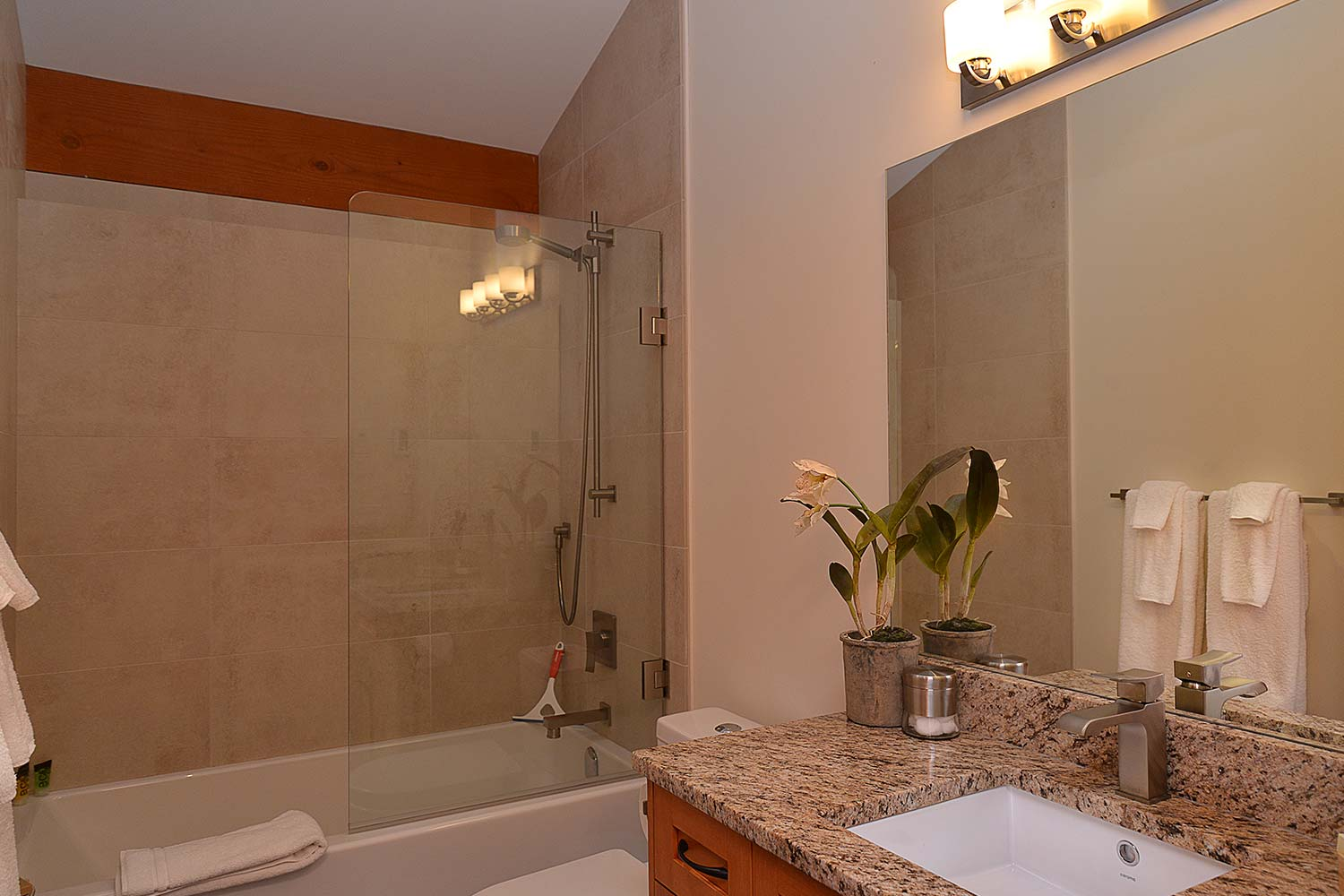 The bathroom of this home for rent by a private owner features a large shower/bath and granite-style countertop.