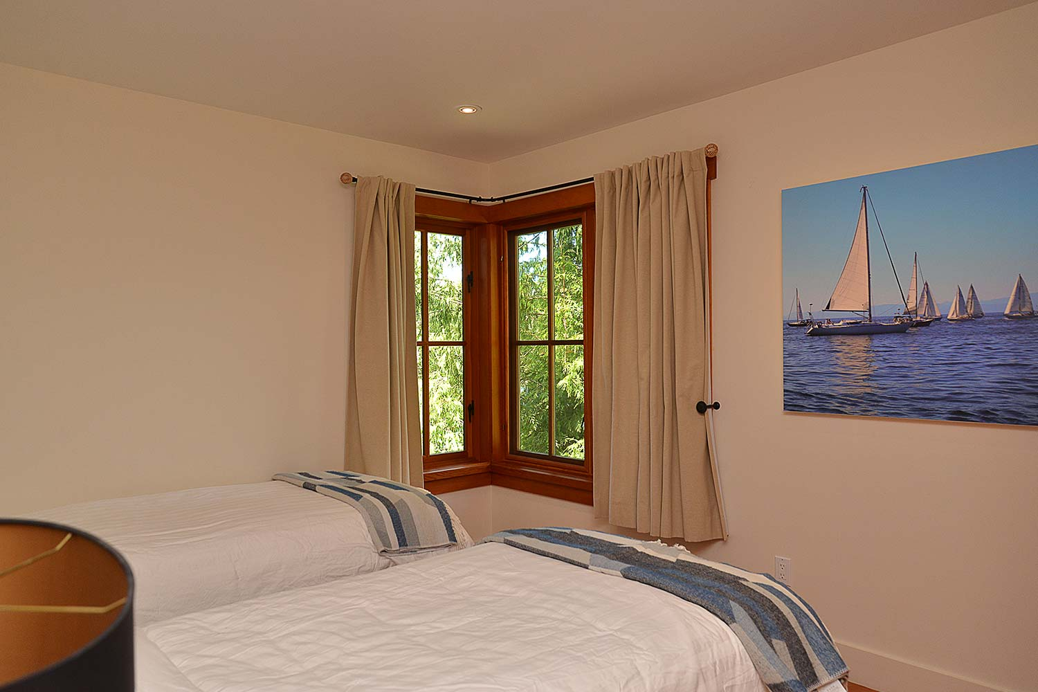 Two single beds in one of the bedrooms of this Pender Harbour resort home. The bedroom has sailing artwork on the wall.
