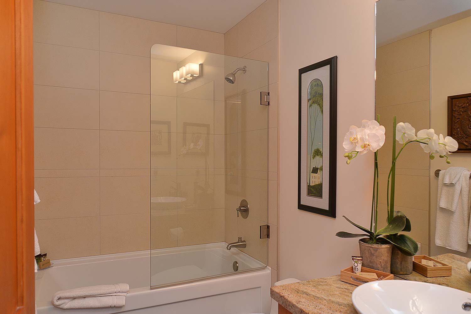 One of the bathrooms of this vacation house rental has a shower with a connected bathtub, artwork on the wall, and flowers.
