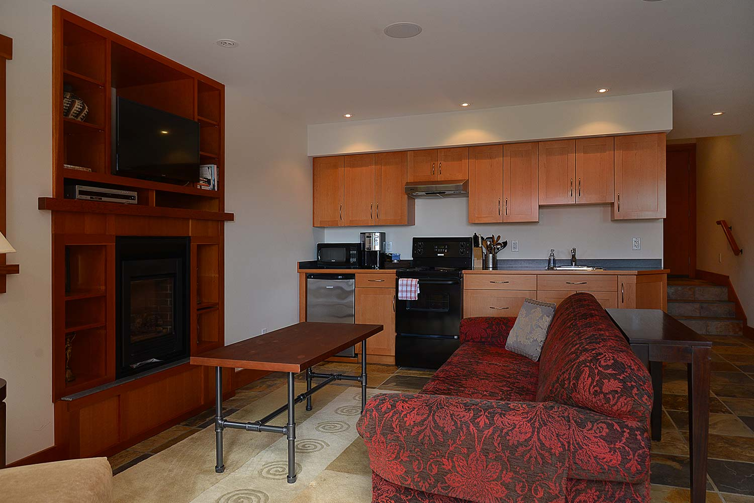 The Garden Suite living room of this luxury furnished rental house features a kitchenette, couch, fridge, dining table, & TV.