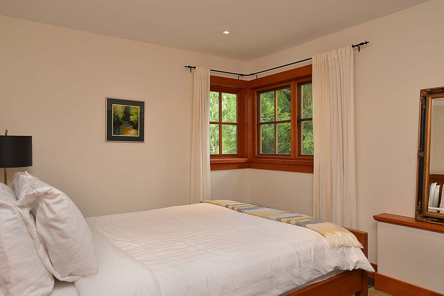 The Garden Suite bedroom at this premium holiday home features a queen bed and adjacent bathroom with a large tub/shower.