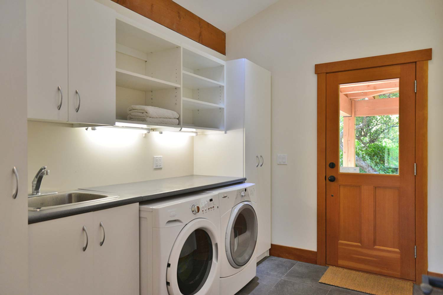 The laundry room at House 65 has a washer & dryer. Laundry soap is included when you stay at this high-end rental home.