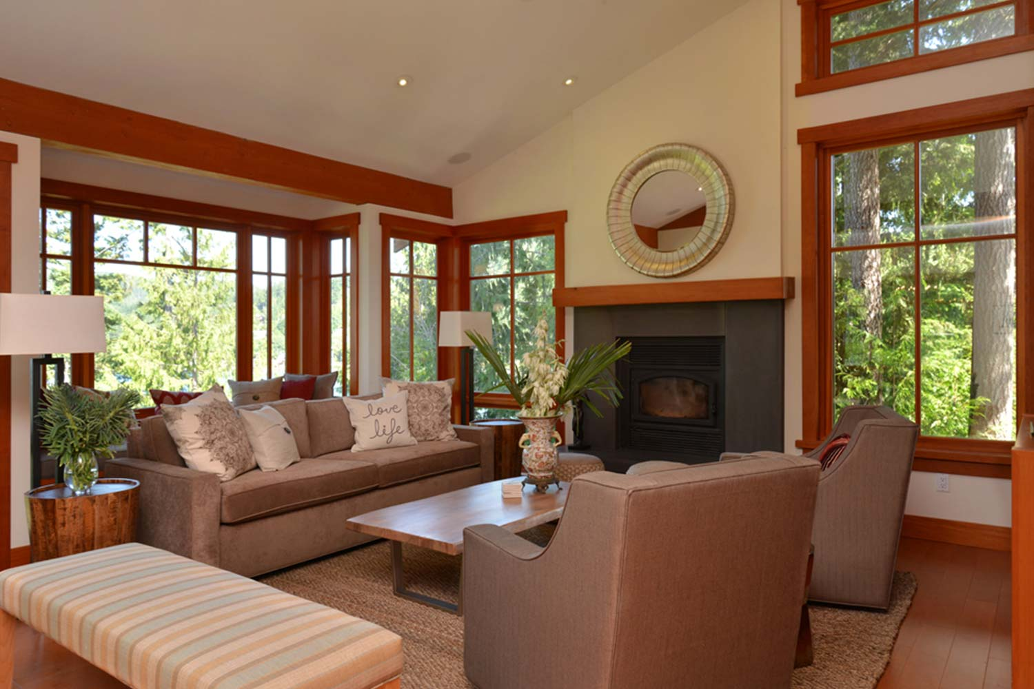 The living room of this high-end rental home in Pender Harbour features a wood burner fire and floor-to-ceiling windows.