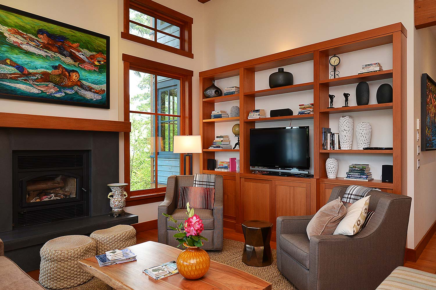 The cozy living area of House 65, a luxury furnished homes for rent with comfortable chairs, artwork, a fire, and a TV.