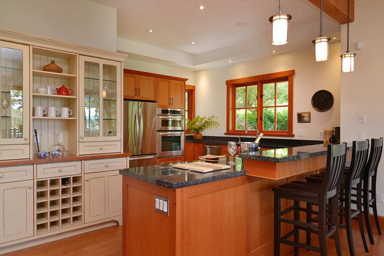 The kitchen of John Henry's luxury holiday home is fully furnished and features a fridge, oven, breakfast bar, and wine rack.