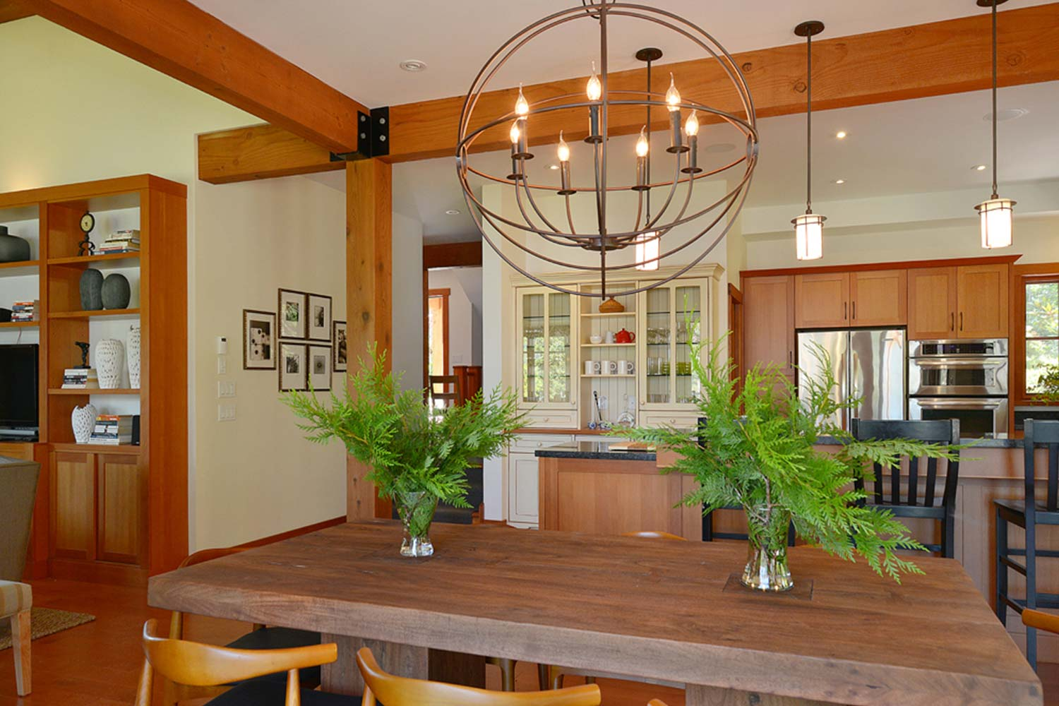 The wooden dining table in this premium holiday home seats up to 8 people and is next to the well-equipped gourmet kitchen.