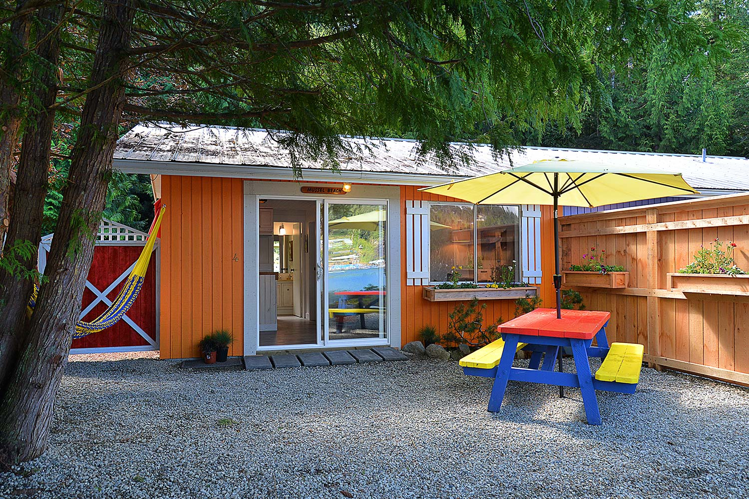 The outdoor view of John Henry's Pender Harbour cottage accommodation features a BBQ, hammock, multi-colour picnic table, and umbrella.