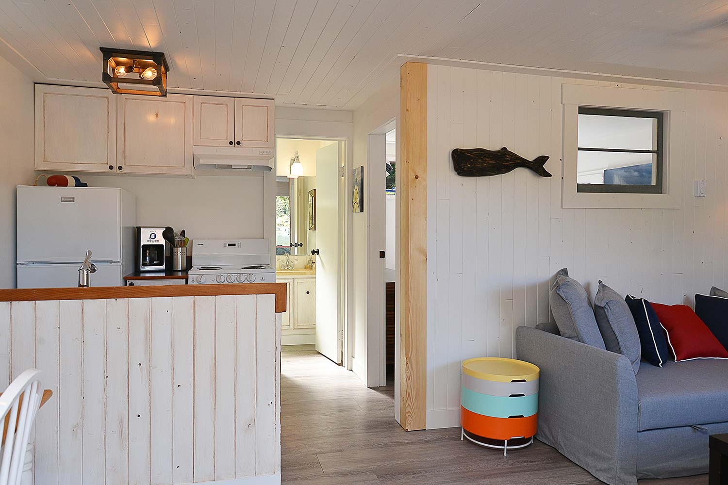 The kitchenette, hallway, and living room in the Mussel Beach waterfront cottage at John Henry's Resort.