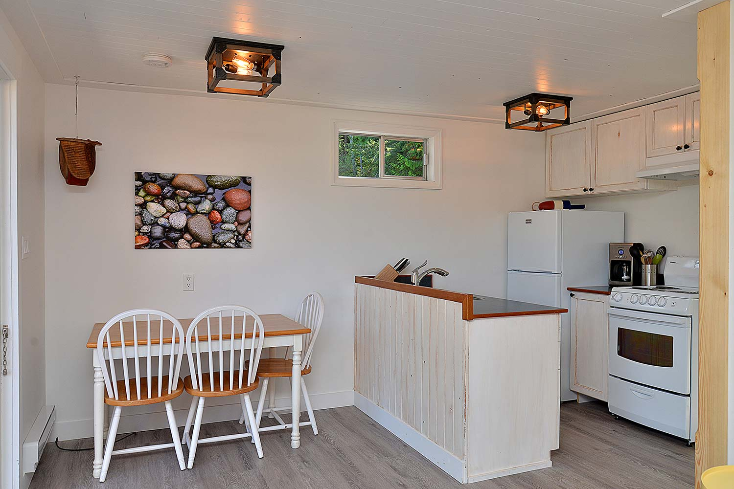 The kitchenette and dining table in this shoreline cottage. The kitchen features a coffee maker, stove & refrigerator.