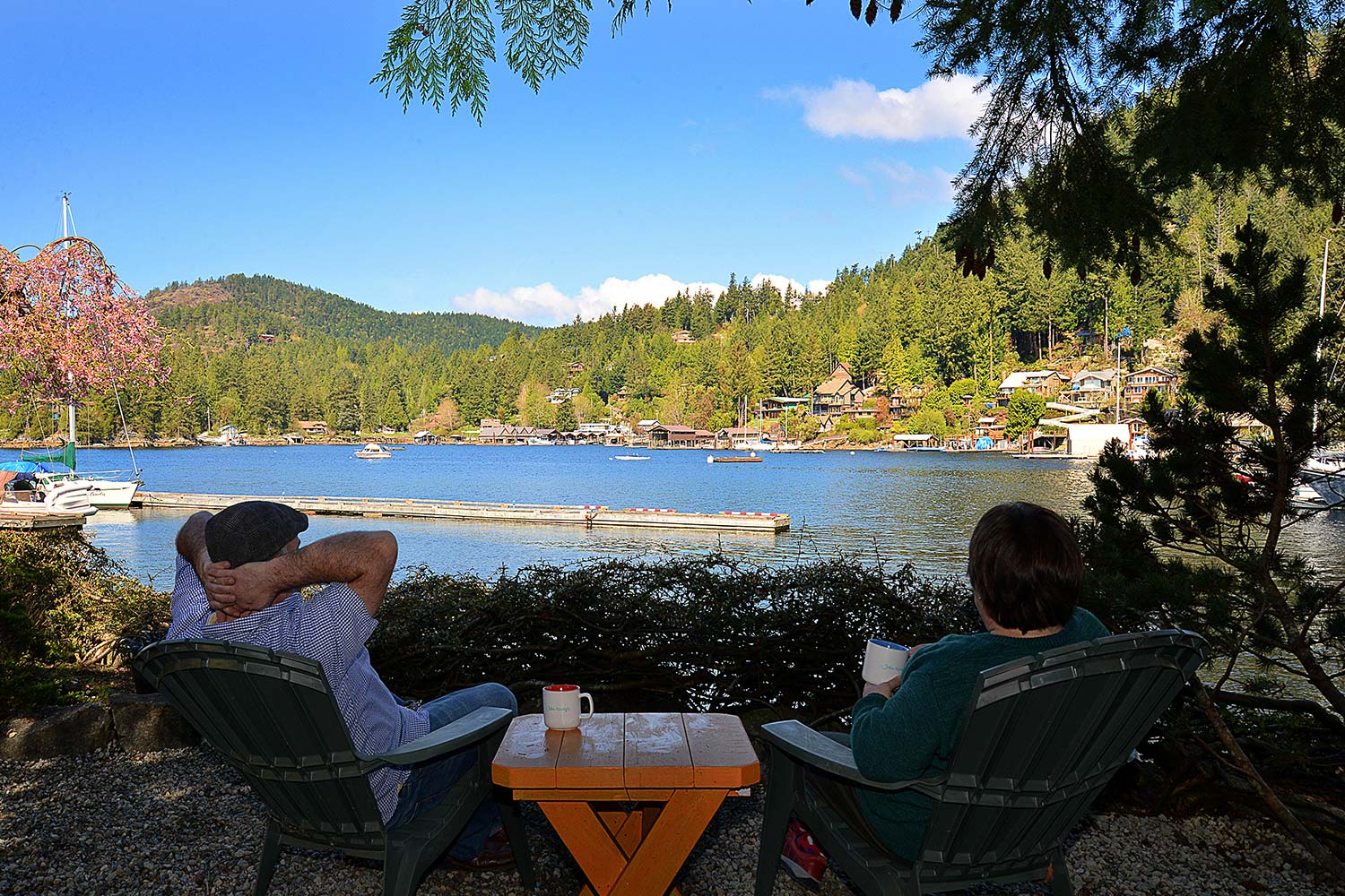 Two guests sit and enjoy a cup of coffee and a scenic view of the Pender Harbour at a waterfront cottage for rent.