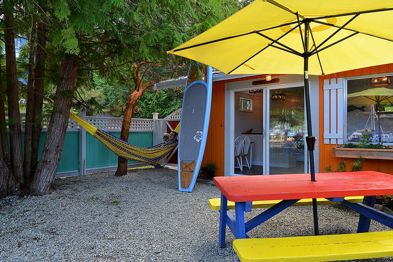 A person relaxes in the hammock next to the orange-coloured Mussel Beach Sunshine Coast cottage rental at John Henry's Resort.