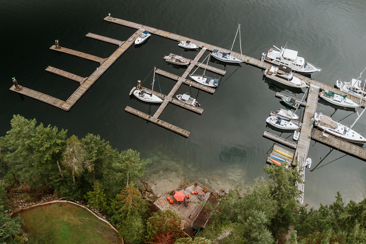 Aerial view of 15 boats on the 2300 lineal feet of boat moorage in Pender Harbour at John Henry's Marina and Resort.