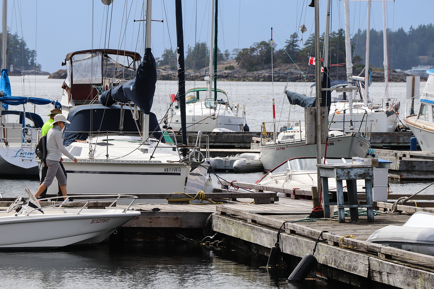 Two boaters using John Henry's marina dock walk among moored boats on the Pender Harbour.