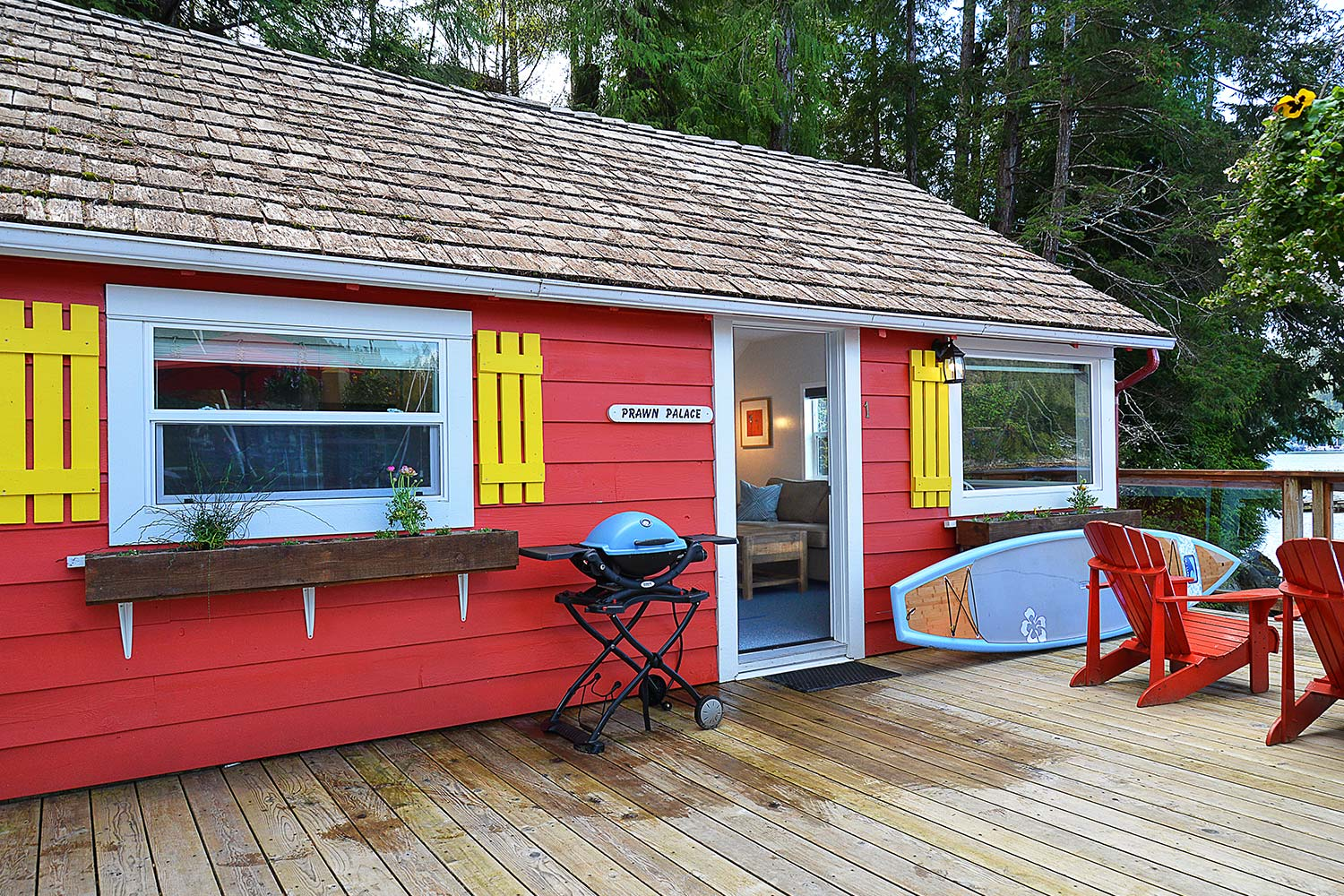A Weber BBQ and stand-up paddleboard on the front deck of Prawn Palace. A cute cottage situated over the Pender Harbour.
