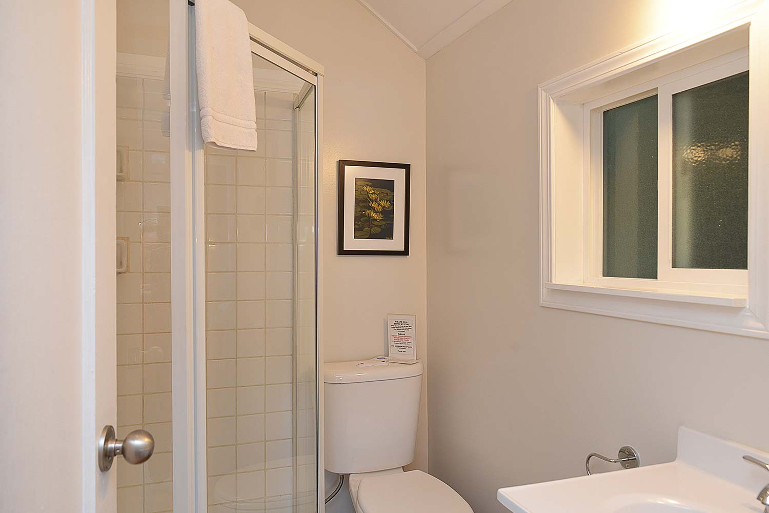 The toilet and shower in the bathroom of Prawn Palace. A Sunshine Coast, British Columbia vacation rental cottage.
