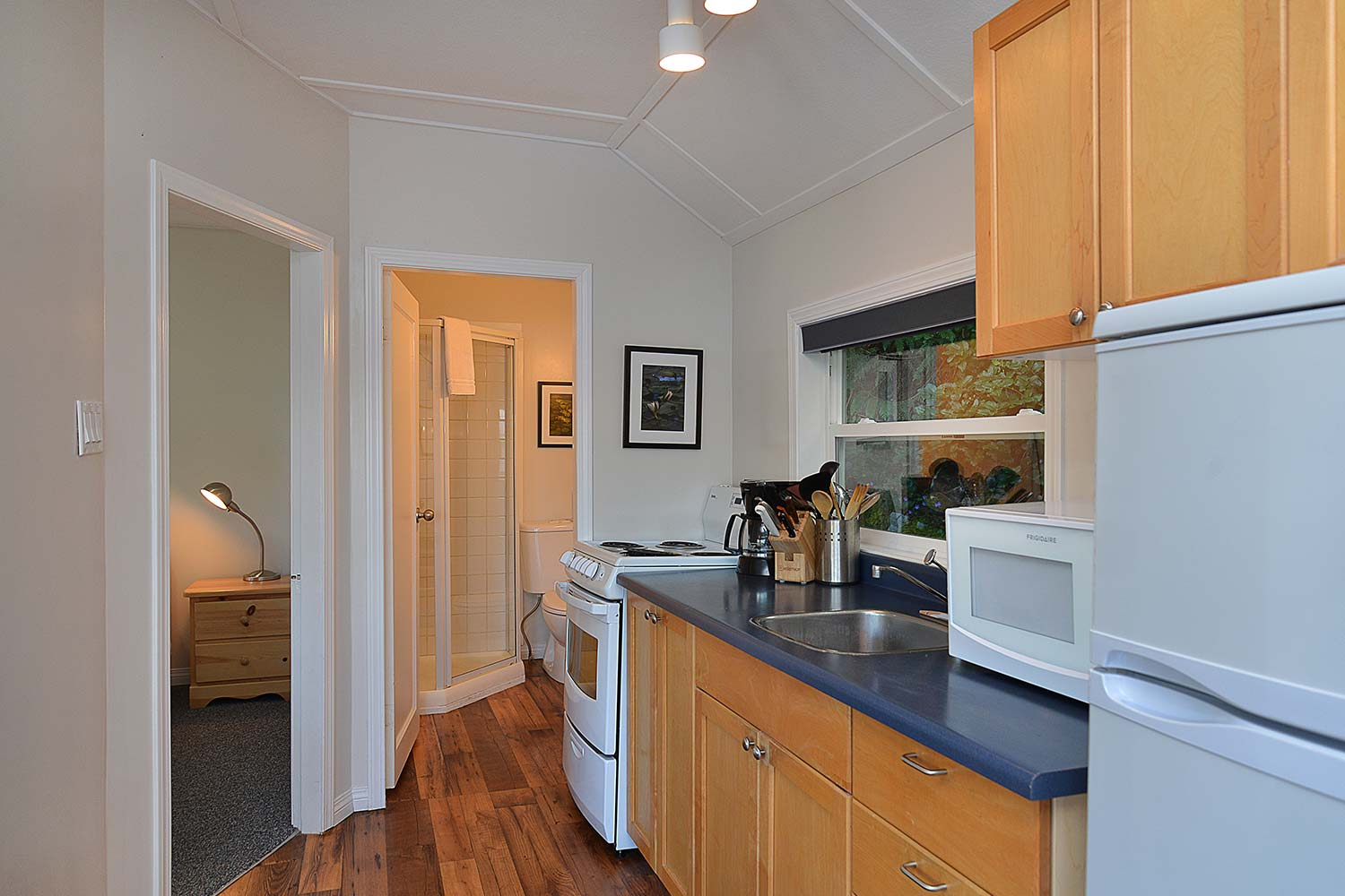 The fully furnished kitchenette and bathroom of the 1-Bedroom Prawn Palace weekend cottage.