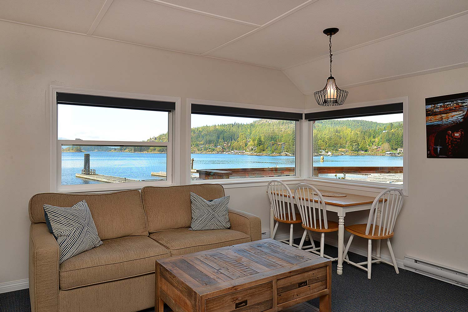 The Prawn Palace living room has a pull-out sofa bed and a coffee table, and features incredible views of Pender Harbour.