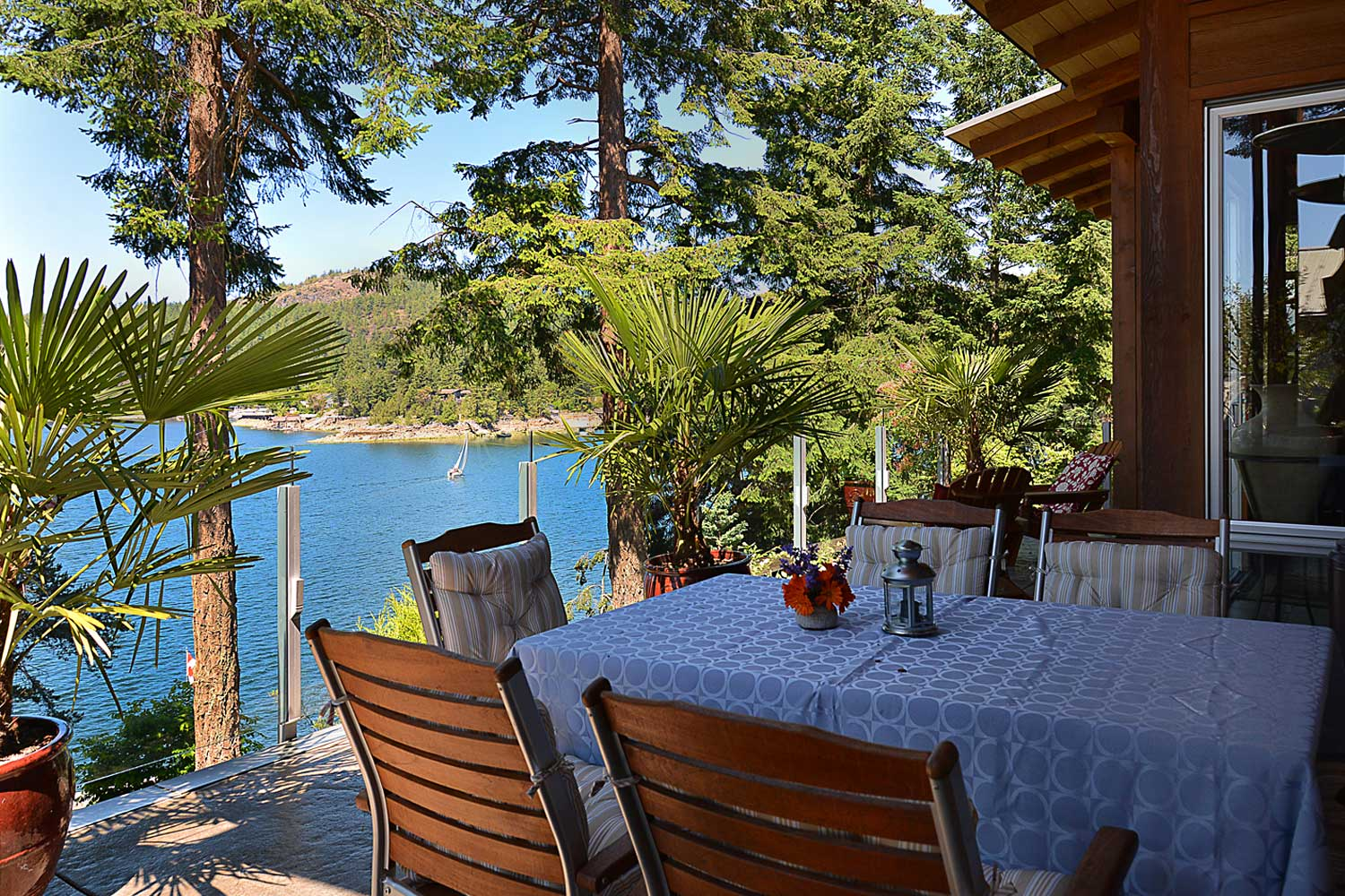 A sailboat can be seen cruising on the water from the outdoor dining area of this Pender Harbour accommodation.