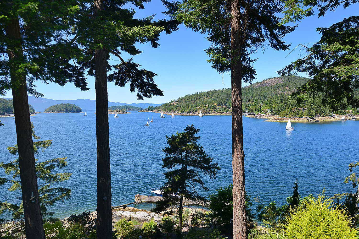 A spectacular view of Pender Harbour, filled with colourful sailboats, is seen from the main floor balcony of this oceanfront house rental.