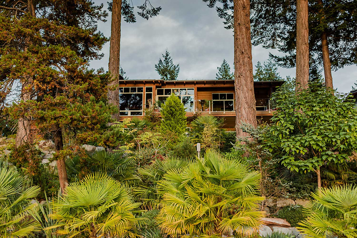 A view from the shoreline of a luxury Pender Harbour vacation rental and its exceptionally well landscaped front garden.