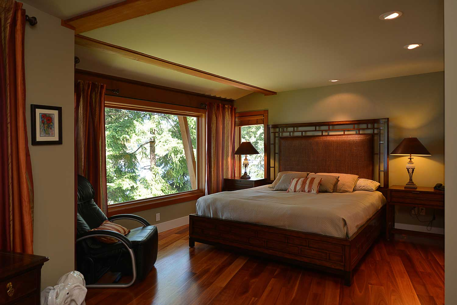 The large master bedroom of this short-term luxury rental in Sunshine Coast, BC features a king bed and walk-in wardrobe.