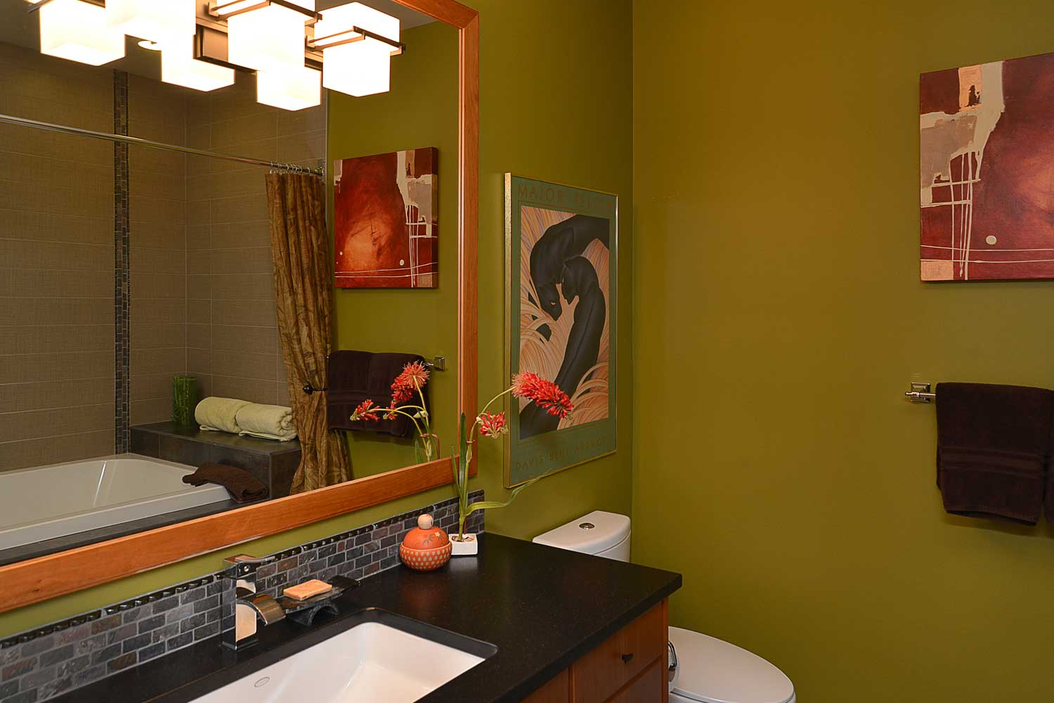 Artwork, flowers, and a large mirror can be found in the master bathroom of this 4 bedroom home for rent.