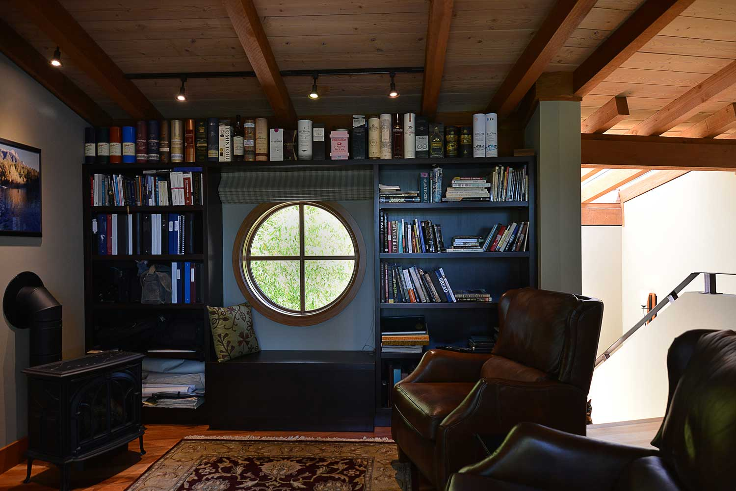 The master upstairs office of this luxury furnished rental house has a window bench seat, leather seats, and a bookcase.