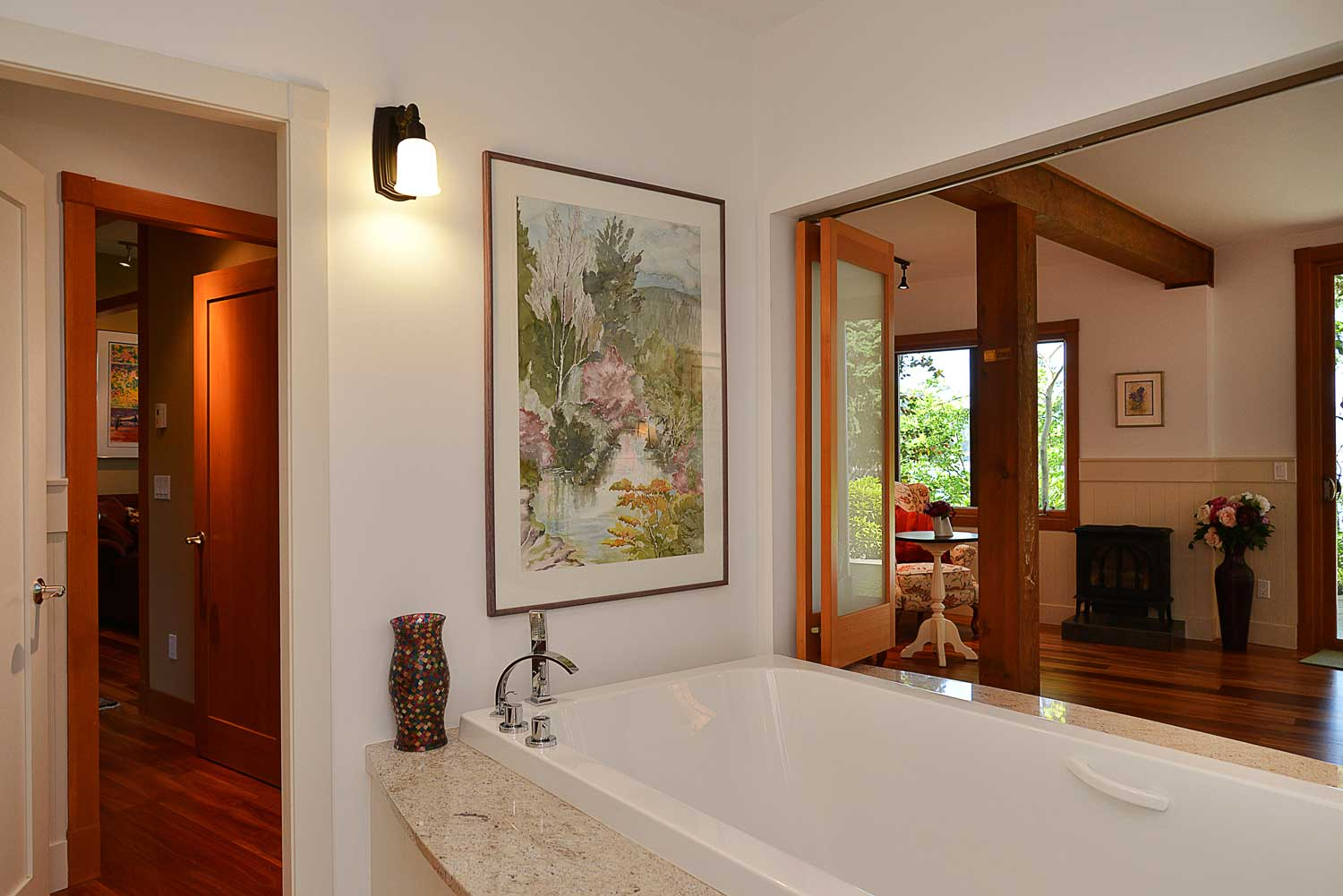 This fully furnished house for rent has a tub in the downstairs bathroom with a window that opens to view into the bedroom.