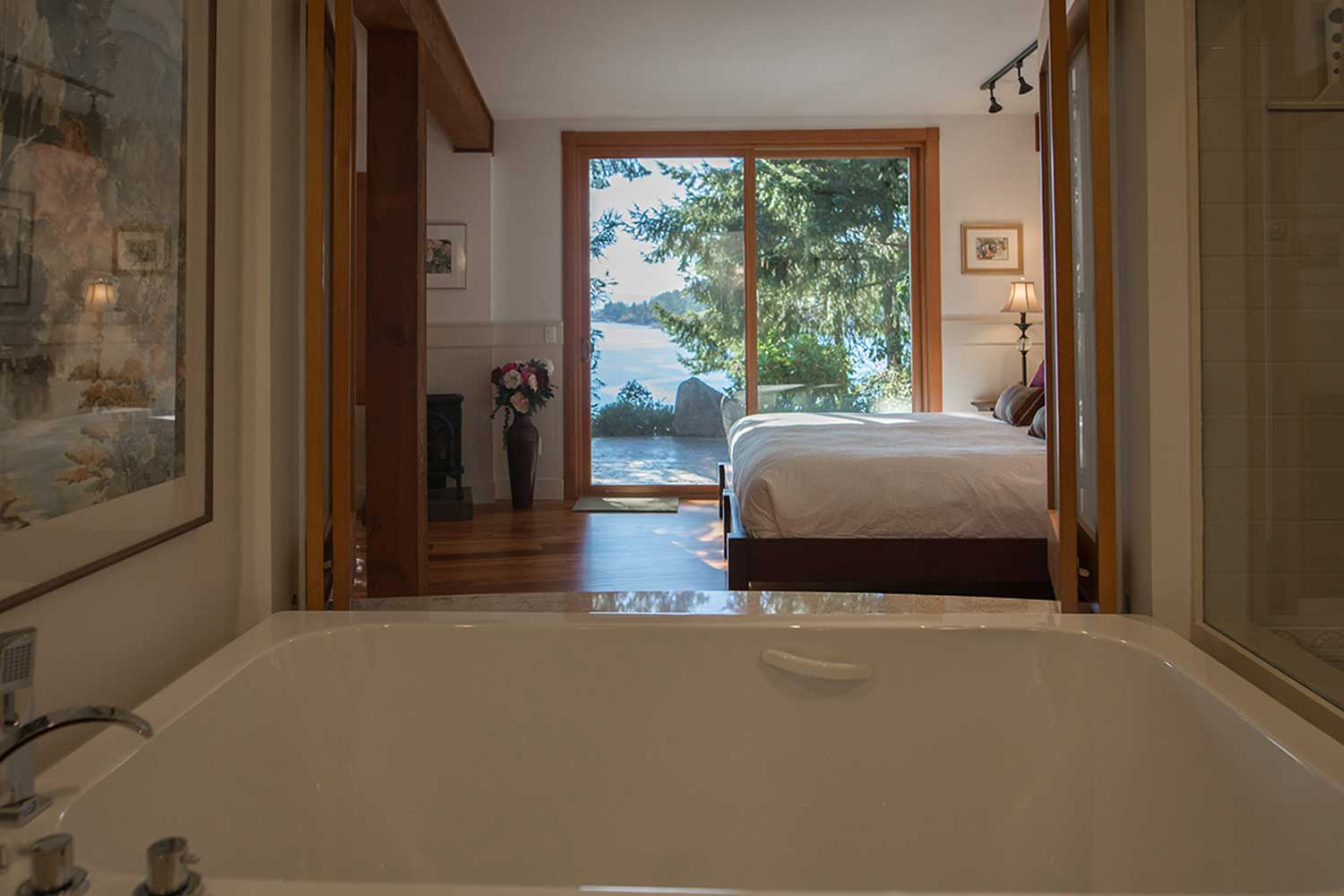 A view through the downstairs master bedroom to the Pender Harbour from the tub in this luxury holiday house.