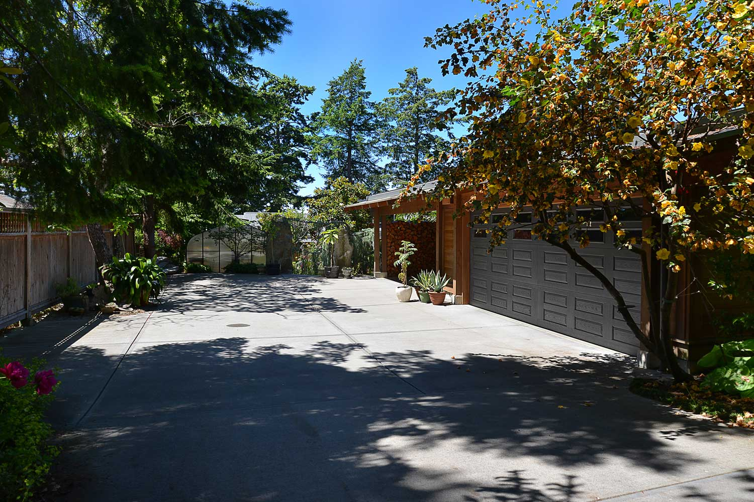 This private, premium holiday home features a dual garage, courtyard, and plenty of firewood at the end of the driveway.