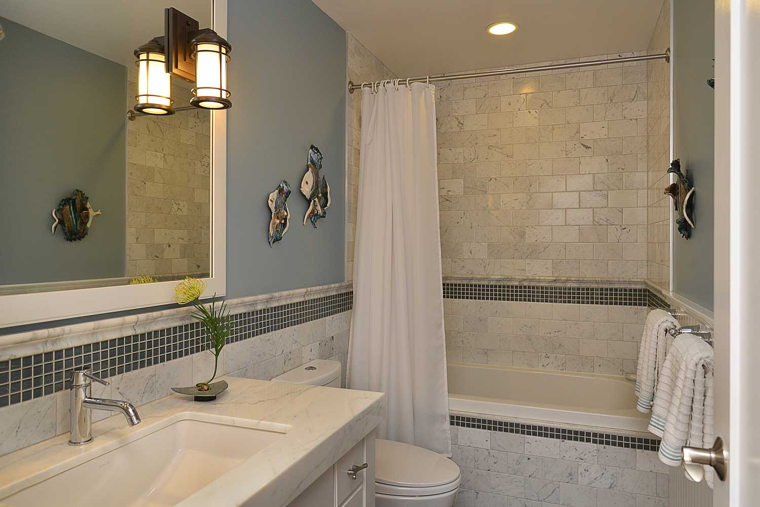 A white tiled bathroom with a sink, shower, and tub connected to one of the bedrooms in this 4-bed house to rent.