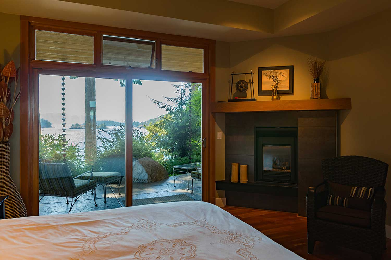 A view of the outdoor patio and the stunning Pender Harbour from a bedroom in this luxury holiday home to rent.