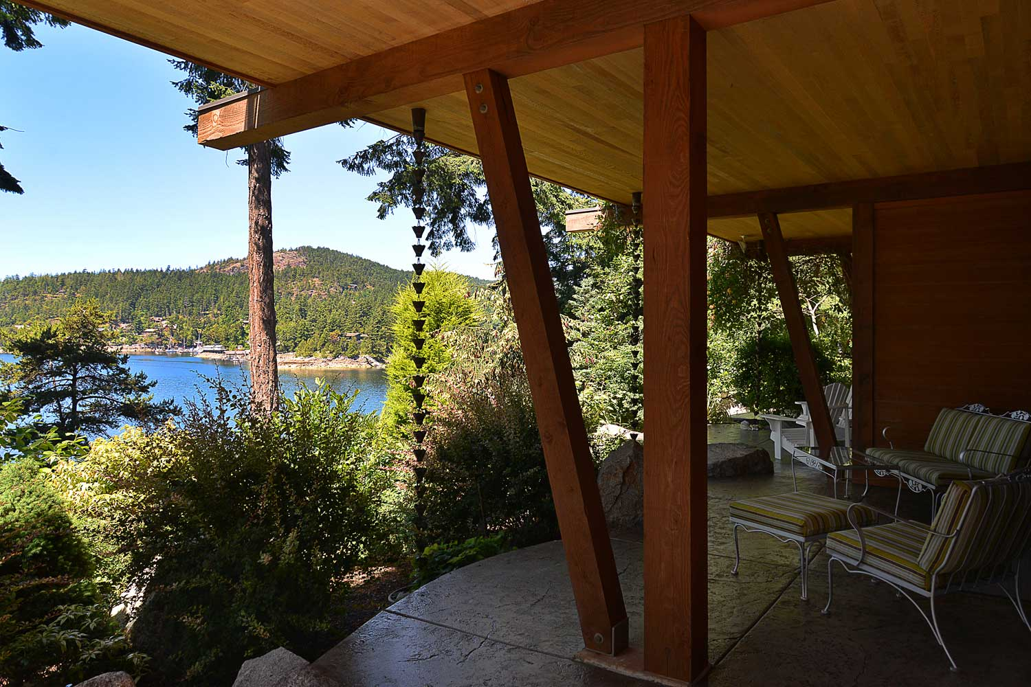 Patio with lounge chairs overlooking the water at the Pender harbour house rental at John Henry's Marina and Resort.