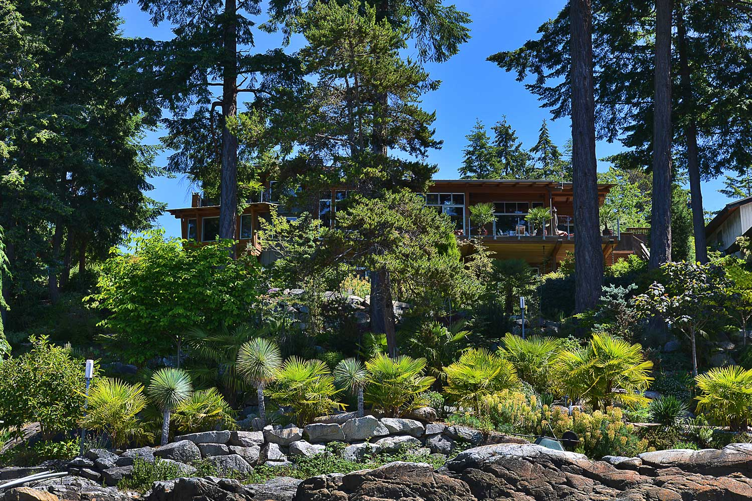 View from the shoreline of the 4 bedroom home for rent near Pender Harbour and its beautiful garden at John Henry's Resort.