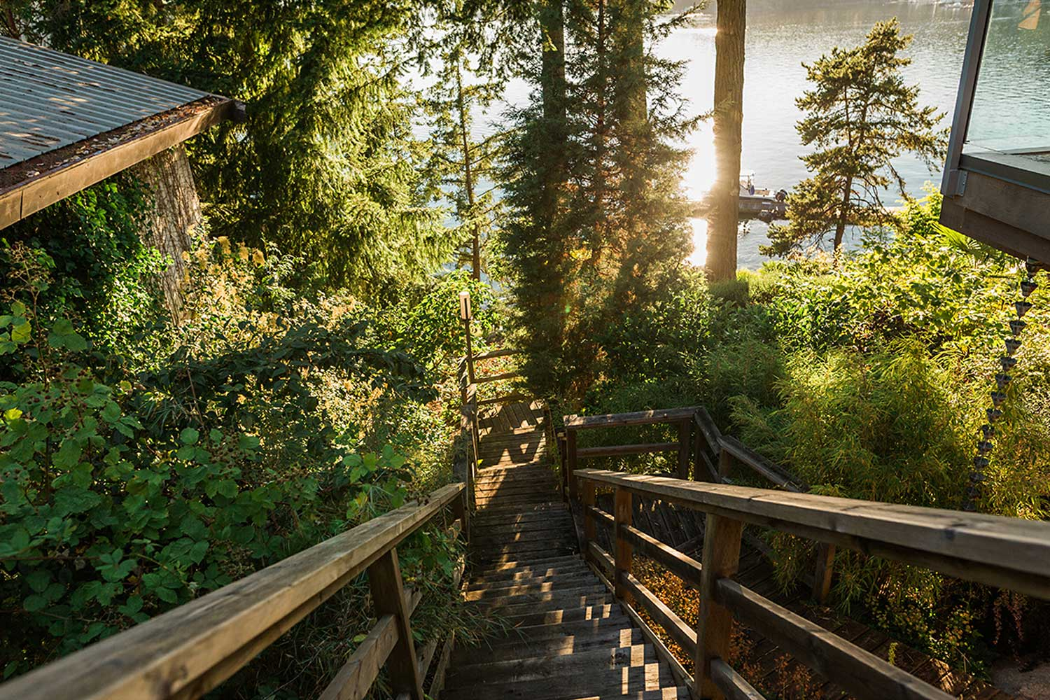 Wooden stairs from the house down through the garden to the shoreline at this luxurious Pender Harbour rental house.
