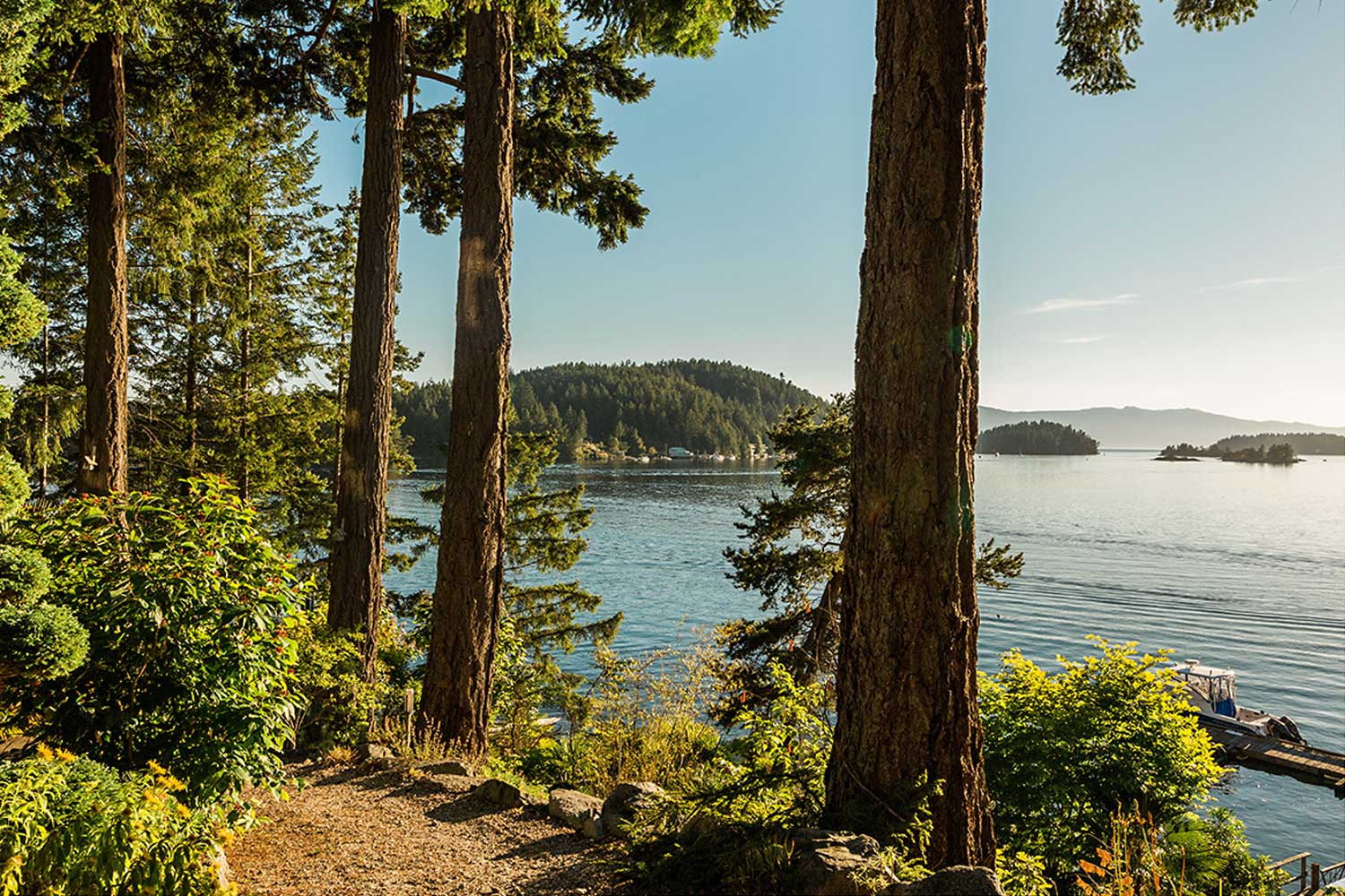 A garden path winds along the shoreline with the ocean to the right at this gorgeous Pender Harbour resort.