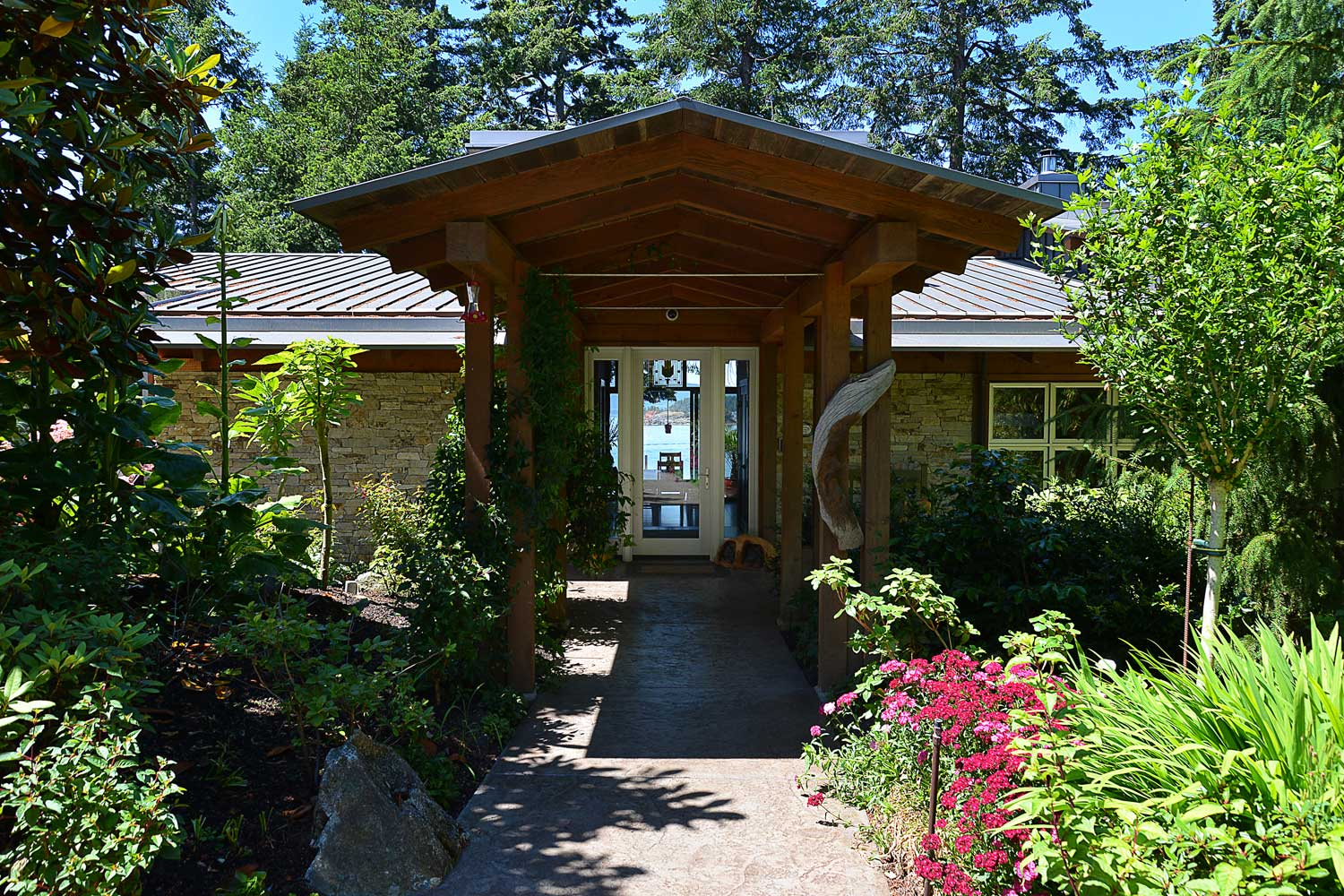 The magnificent front door entry of this luxury holiday home features glass windows where you can see Pender Harbour.