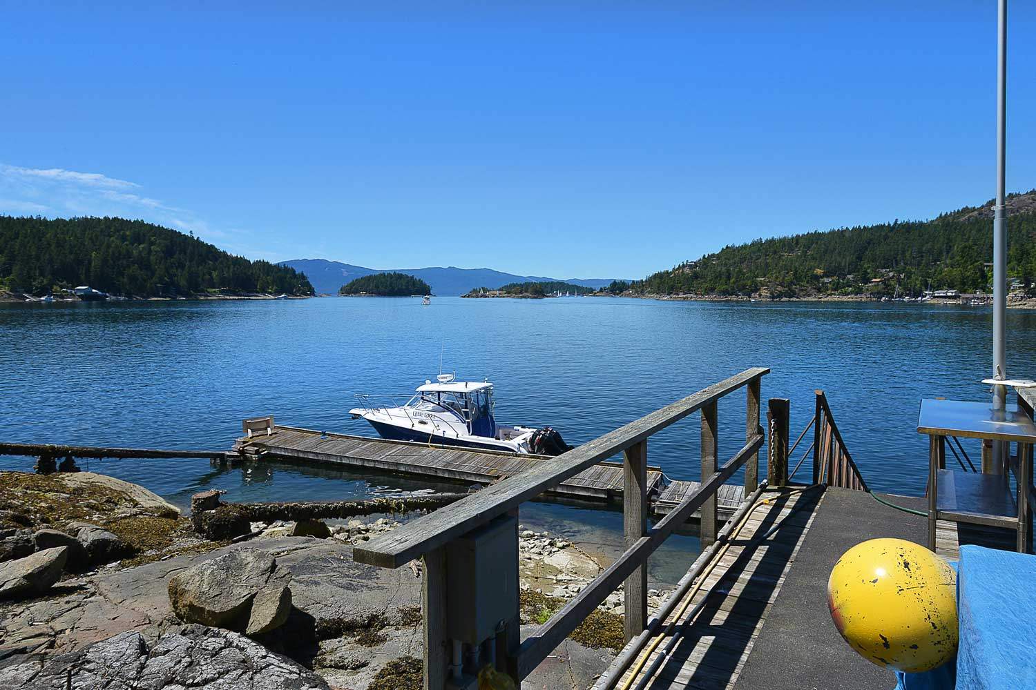A single boat is moored at a private dock on the Pender Harbour. The dock is for guests at the luxury vacation House 63.