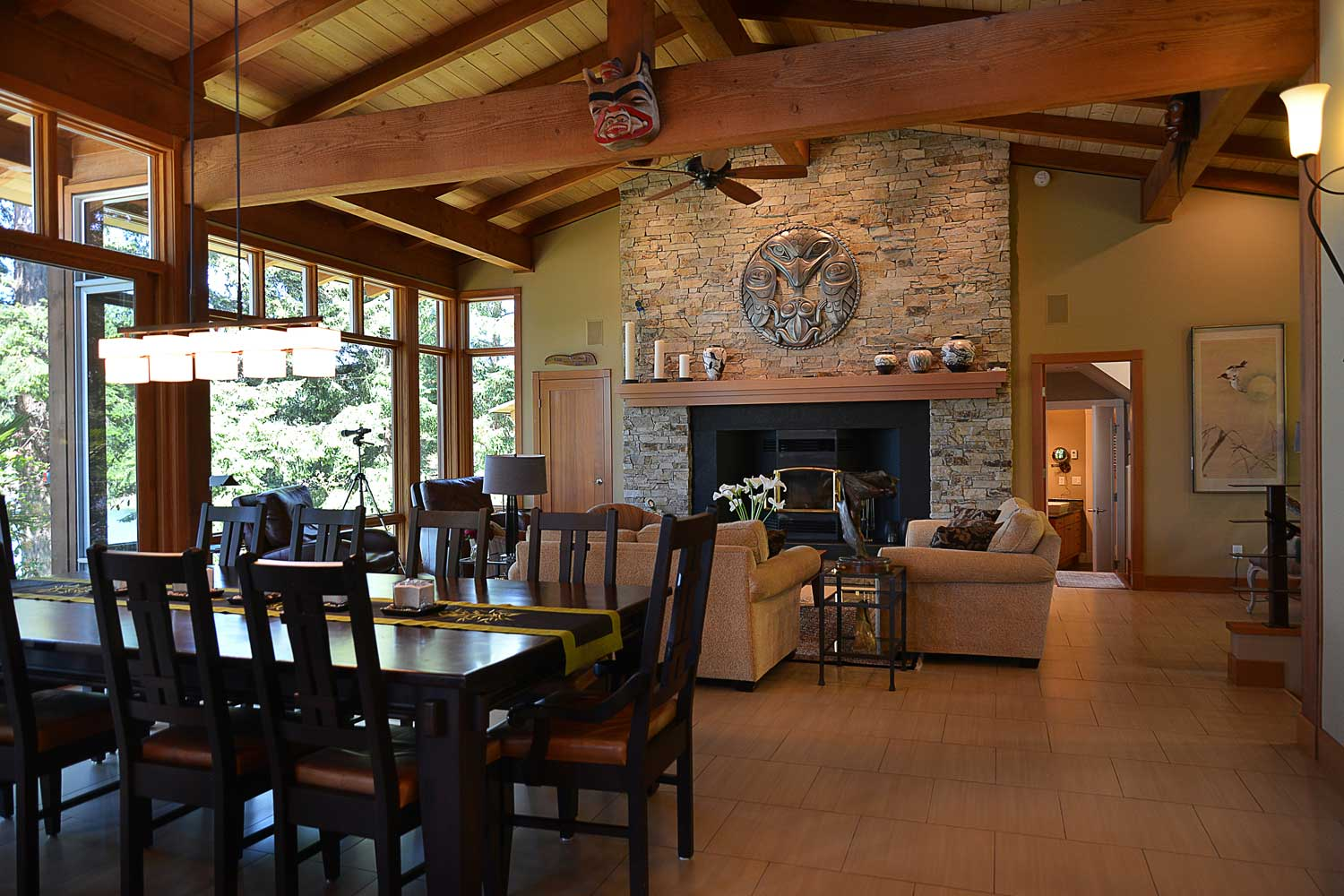 The dining room and living area of this high-end rental home feature an incredible wood-burning fire and authentic First Nations artwork.