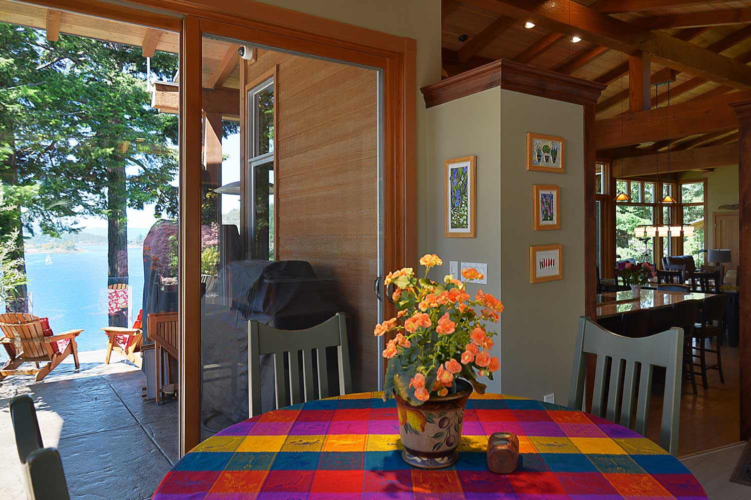 A small table with a colorful tablecloth in the breakfast nook on the main floor overlooks the bright blue Pender Harbour.